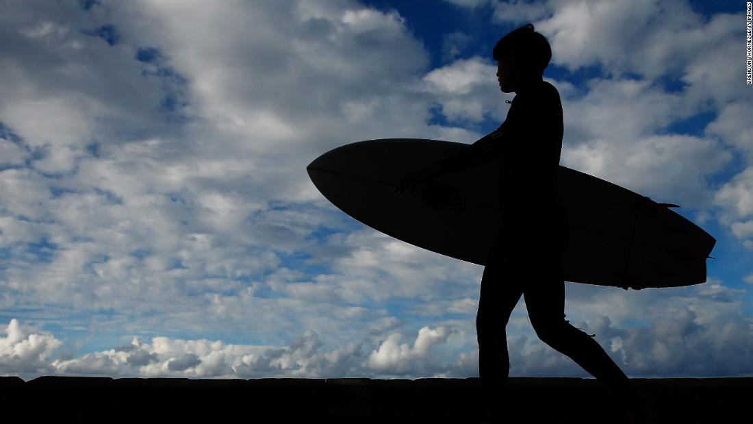 A man walks toward a Sydney beach with a surfboard on Thursday, June 2.