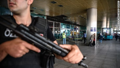 A Turkish anti-riot police officer stands guard as people pass near the explosion site on June 29 at Istanbul Ataturk Airport arrival terminal in Turkey, a day after a suicide bombing and gun attack.