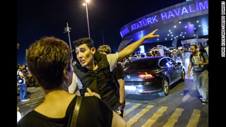 A Turkish police officer directs a passenger at the airport on June 28.