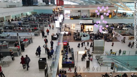 Passengers pass through the security check and walk through the shops inside Terminal 5 at Heathrow Airport.
