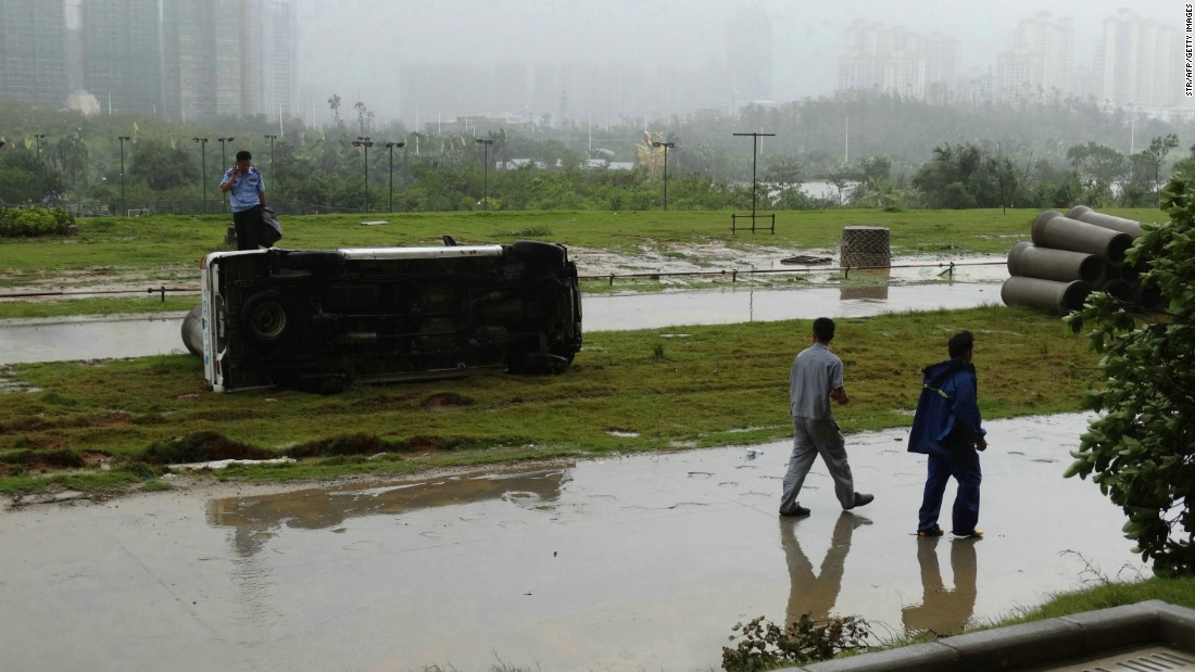 This photograph taken on October 4, 2015 shows people walking past an overturned car after typhoon Mujigae swept the area in Zhanjiang, south China's Guangdong province. Tornadoes spawned by a typhoon that battered southern China left at least seven people dead and more than 200 injured.