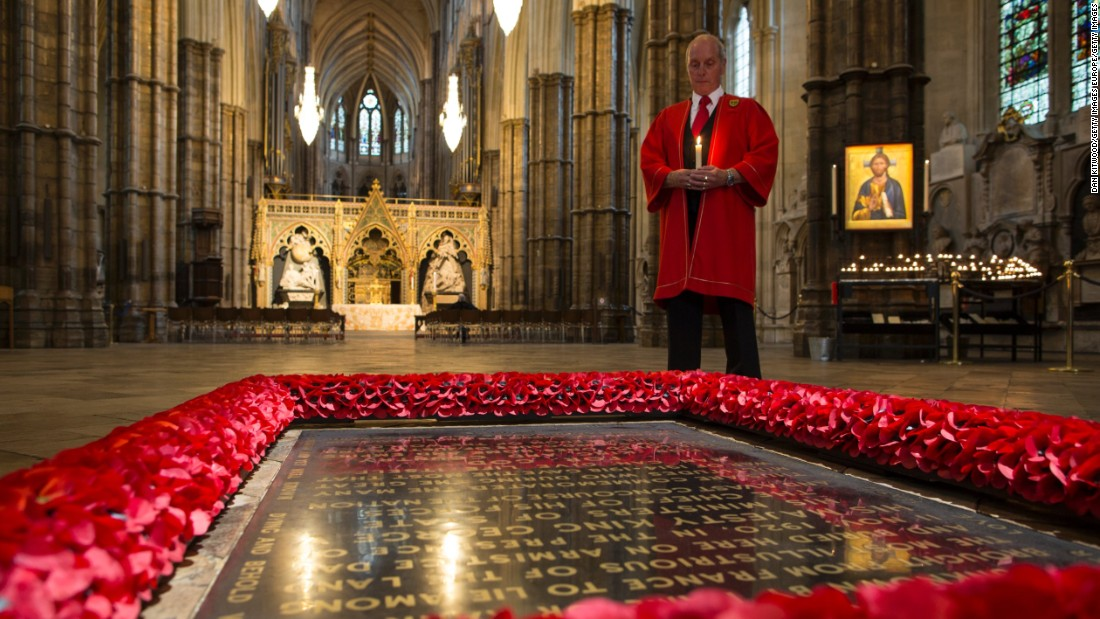 """An abbey marshal poses next to """"The Grave of the Unknown Warrior"""" in London's Westminster Abbey."""