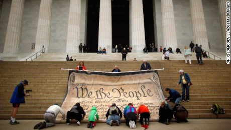 Volunteers help roll up a giant banner printed with the Preamble to the Constitution.