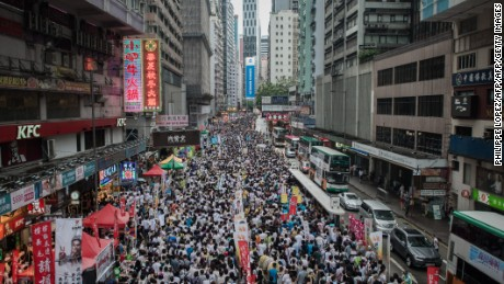"Demonstrators march during a pro-democracy rally seeking greater democracy in Hong Kong on July 1, 2014 as frustration grows over the influence of Beijing on the city.  July 1 is traditionally a day of protest in Hong Kong and also marks the anniversary of the handover from Britain to China in 1997, under a ""one country, two systems"" agreement. AFP PHOTO / Philippe Lopez        (Photo credit should read PHILIPPE LOPEZ/AFP/Getty Images)"
