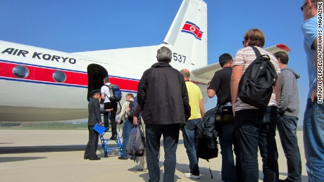 A tour group of about 75 aviation enthusiasts lines up to board a rare Air Koryo airliner.