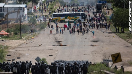 Members of Mexican Federal Police clash with teachers holding a protest against an education reform and the arrest of two of their leaders, in Oaxaca State, on June 19, 2016.  At least three people were killed and dozens injured when police clashed with thousands of teachers blocking roads in a protest in southern Mexico on Sunday, leaving some officers with bullet wounds. / AFP / STR        (Photo credit should read STR/AFP/Getty Images)