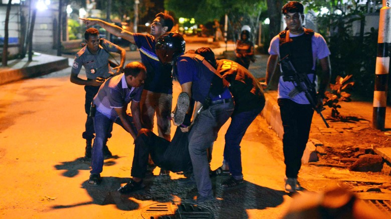 People help an unidentified injured person after a group of gunmen attacked a restaurant popular with foreigners in a diplomatic zone of the Bangladeshi capital Dhaka, Bangladesh, Friday, July 1, 2016. A group of gunmen attacked a restaurant popular with foreigners in a diplomatic zone of the Bangladeshi capital on Friday night, taking hostages and exchanging gunfire with security forces, according to a restaurant staff member and local media reports.