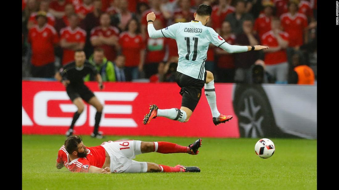 Yannick Ferreira Carrasco jumps past Wales' Joe Ledley.