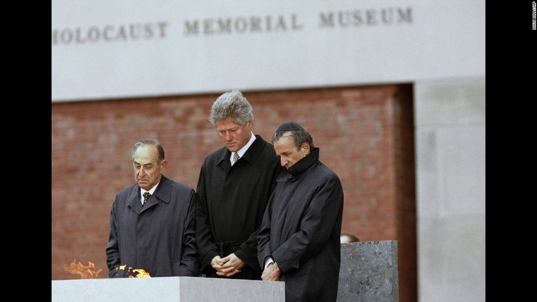 Elie Wiesel, right, stands beside then-President Bill Clinton, center, and Bud Meyerhoff, left, chairman of the U.S. Holocaust Memorial Council, after lighting the eternal flame during the dedication ceremony for the U.S. Holocaust Memorial Museum in Washington, April 22, 1993.