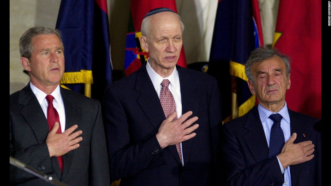 Then-President George Bush, left; Rabbi Irving Greenberg, center; and Elie Wiesel, right, sing the national anthem during a national commemoration of the Days of Remembrance for victims of the Holocaust, in the Capitol rotunda on April 19, 2001, in Washington.