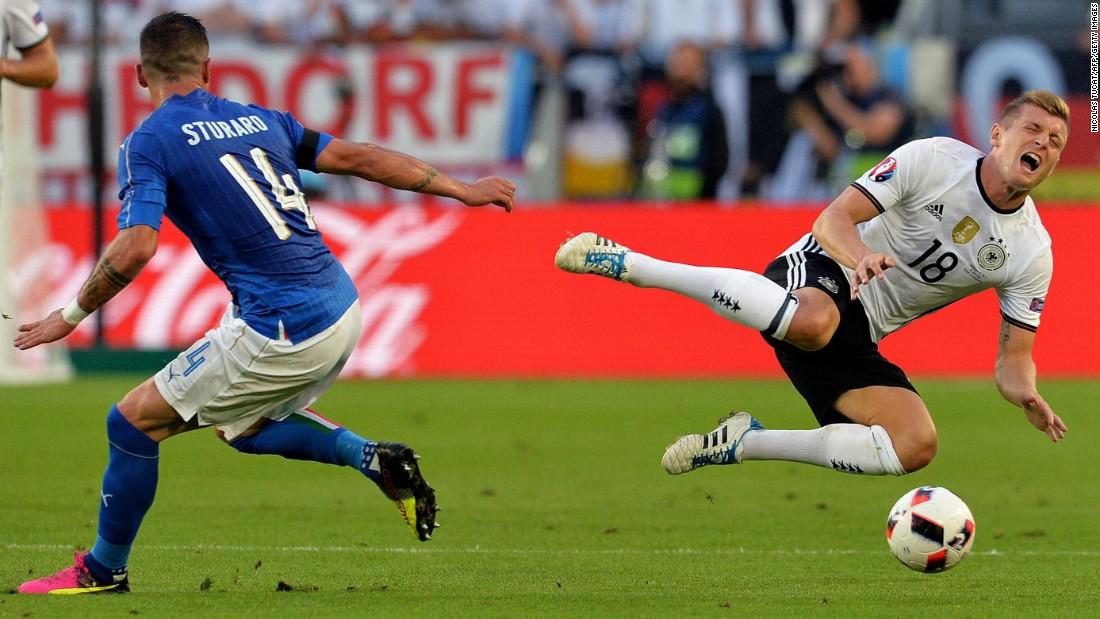 Italy midfielder Stefano Sturaro looks on as Germany midfielder Toni Kroos goes flying.
