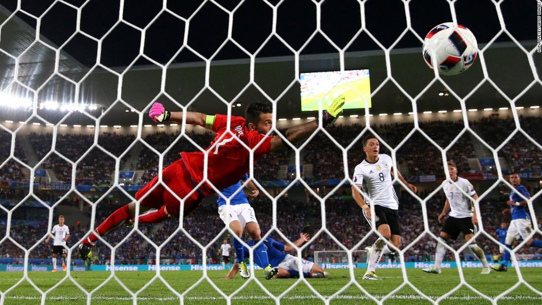 The ball flies past Gianluigi Buffon of Italy as he tries to block Mesut Oezil's opening goal.