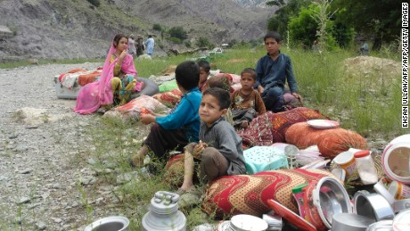 Pakistani children affected by flooding sit on higher ground in the village of Nagar in Chitral on July 3, 2016.