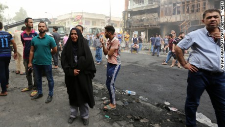 """Iraqis react at the site of a suicide car bombing claimed by the Islamic State group on July 3, 2016 in Baghdad's central Karrada district. The blast, which ripped through a street in the Karrada area where many people go to shop ahead of the holiday marking the end of the Muslim fasting month of Ramadan, killed at least 75 people and also wounded more than 130 people, security and medical officials said. The Islamic State group issued a statement claiming the suicide car bombing, saying it was carried out by an Iraqi as part of the group's """"ongoing security operations"""". / AFP / SABAH ARAR        (Photo credit should read SABAH ARAR/AFP/Getty Images)"""