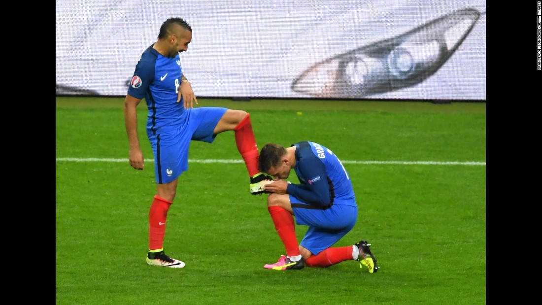 France's forward Dimitri Payet's shoe is kissed by teammate forward Antoine Griezmann as they celebrate France's third goal.