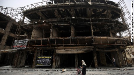 An Iraqi woman walks a building that was damaged during the by a suicide-bombing.