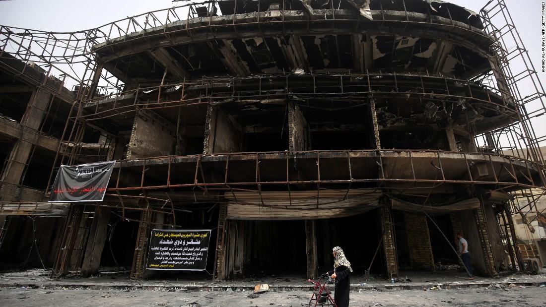 A woman walks by a building that was damaged in the Karrada blast.