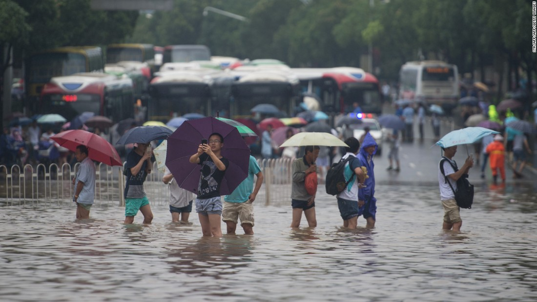 People cross a seriously flooded street in Wuhan, in China's central Hubei province on July 2, 2016<strong>.</strong>