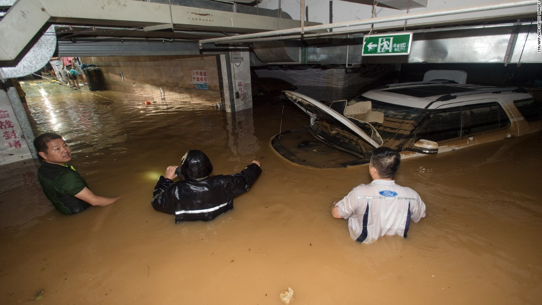 Residents try to remove a car from a flooded parking garage in Wuhan, July 2. <br />