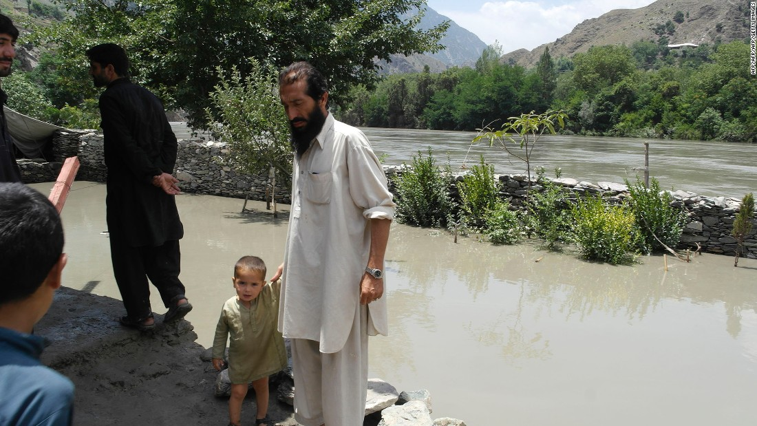 Pakistani residents affected by sudden flooding gather on higher ground alongside deep flood waters in the village of Nagar in Chitral on July 3, 2016.