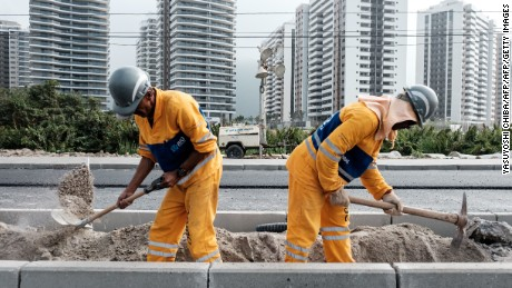 "Workers build a new road called ""Transolimpica"" that connect Barra da Tijuca and Deodoro, two major Olympic and Paralympic areas, including a special lane for the Bus Rapid Transit (BRT) near the Olympic and Paralympic Village in Rio de Janeiro, Brazil, on July 1, 2016. / AFP / YASUYOSHI CHIBA        (Photo credit should read YASUYOSHI CHIBA/AFP/Getty Images)"
