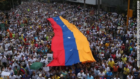 CARACAS, VENEZUELA - MARCH 02:  Carrying a giant Venezuelan flag, thousands of anti-government protesters march during a mass demonstraiton on March 2, 2014 in Caracas, Venezuela. Venezuela has one of the highest inflation rates in the world, and opposition supporters have protested for almost three weeks, virtually paralyzing business in much of the country. (Photo by John Moore/Getty Images)