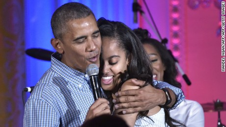 President Barack Obama hugs his daughter Malia on her birthday during an Independence Day Celebration for military members and administration staff on July 4, 2016 in the East Room of the White House in Washington, DC.