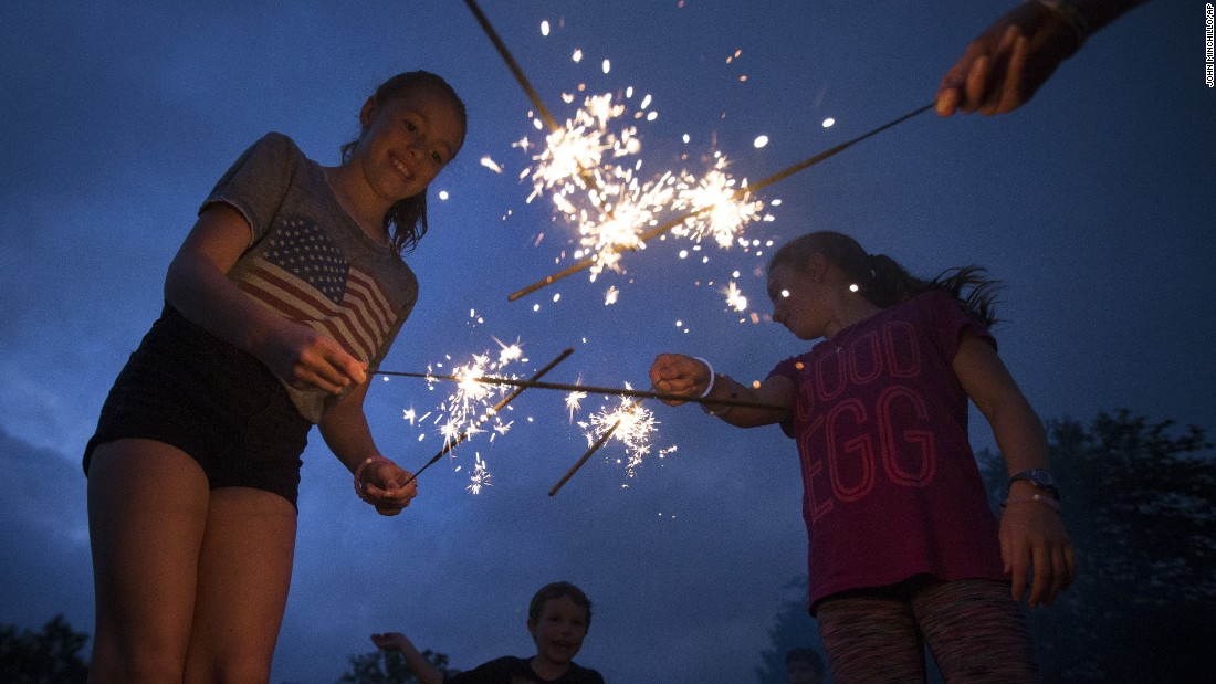 Girls play with sparklers as they wait for fireworks to begin in Cincinnati's Ault Park.