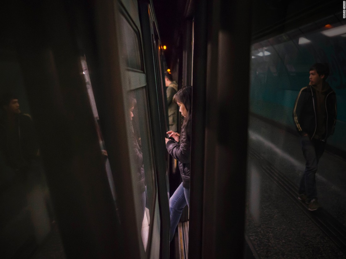 """Singapore-based photographer captured passengers as they moved through the narrow gaps between Hong Kong's subway trains and and platform doors. The compilation documents """"the hustle and bustle of Hong Kong,"""" Chong says."""