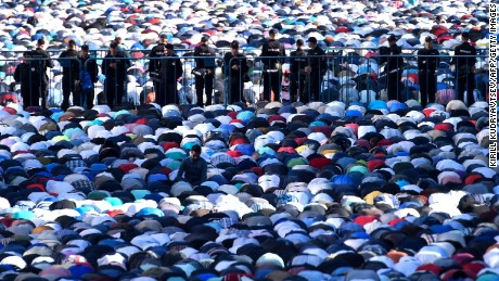 Police stand among Russian Muslims praying outside the central mosque in Moscow on July 5 during celebrations of Eid al-Fitr marking the end of the fasting month of Ramadan.