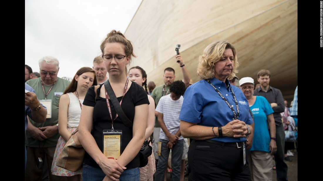 Visitors bow their heads in prayer during a ribbon-cutting ceremony on July 5.