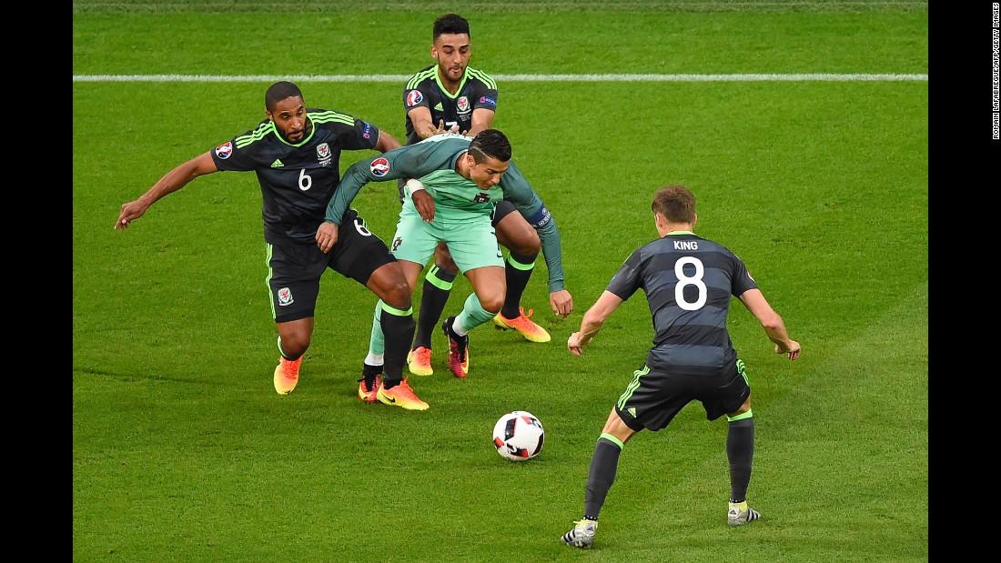 Ronaldo is swarmed by Welsh defenders.
