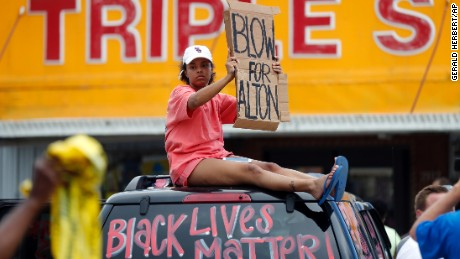 A woman holds up a sign encouraging motorists to honk outside the Triple S convenience store during a rally after Alton Sterling was shot and killed Tuesday.