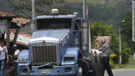 A man takes a picture of a truck damaged by farmers protesting for land reform and increased state spending in rural areas during a blockade of the Panamerican highway in Pescador, department of Cauca, Colombia on June 2, 2016. More than 30,000 peasant farmers in Colombia have joined a growing anti-government protest, blocking roads and engaging in clashes with police that have wounded 28 people, officials said Thursday. / AFP / LUIS ROBAYO        (Photo credit should read LUIS ROBAYO/AFP/Getty Images)