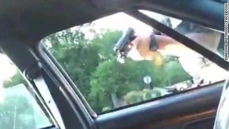 A police officer points a gun through the window of Philando Castile's car window.