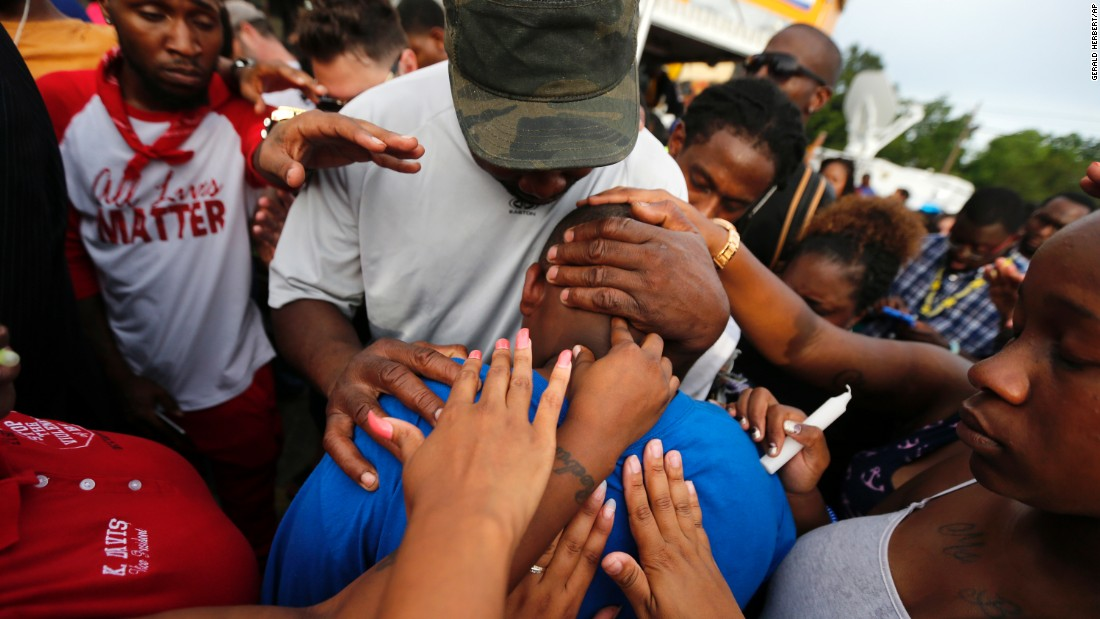 One of Sterling's children, Cameron, is comforted by a crowd outside the convenience store on July 6.
