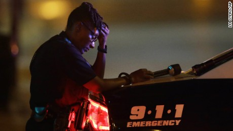 A Dallas police officer takes a moment as she guards an intersection after a shooting in downtown Dallas.