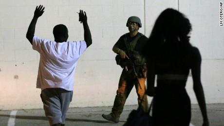 A man raises his hands as he walks near a law enforcement officer, following the shootings Thursday of several police officers in downtown Dallas, early Friday, July 8.