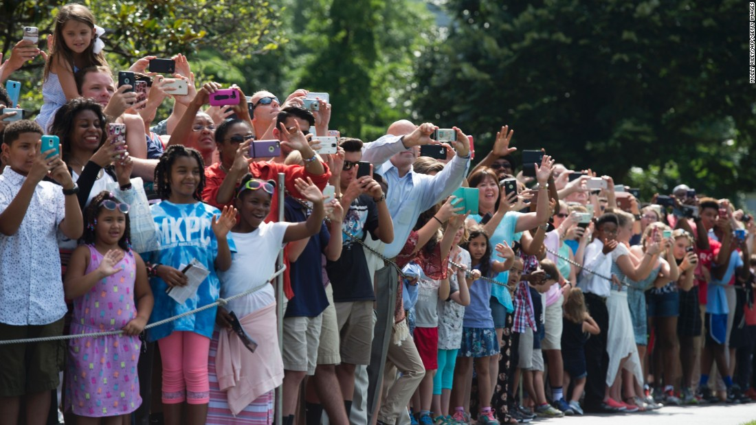 A crowd waves as Obama departs the White House for his trip to Warsaw, Poland, on July 7, in Washington.