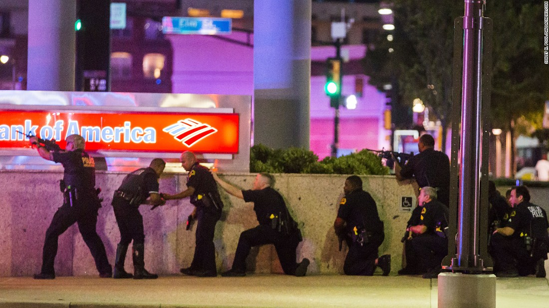 """Dallas Police take position after shots are fired. Pool said the police were """"very focused, very on their game."""" This image, showing a line of officers against the wall with their guns drawn, was made as Pool looked down the street while he was squeezed between some cars and behind a police officer for cover."""