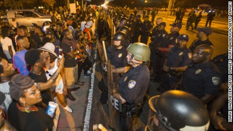 Protesters face off with Baton Rouge police across the street from the police department on Saturday.