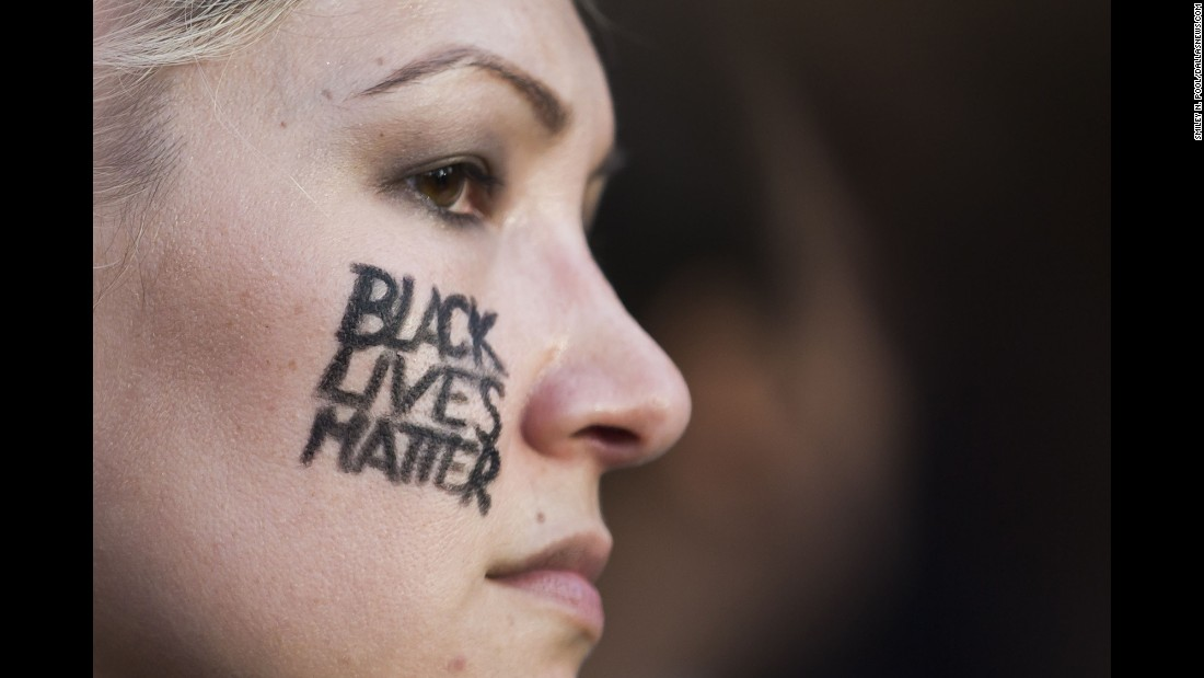 """A woman with """"Black Lives Matter"""" on her cheek joins other protesters. As the march began and although the police presence was considerable, Pool said everyone was positive."""