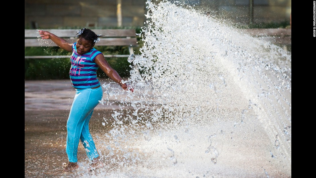"""Jonasha Wright, 8, plays in a fountain a few feet away from a protest rally. """"One of the very first photographs I was making was of a little girl spinning and twirling and smiling and laughing in a fountain in the park where the rally was. There she was, a few feet from this Black Lives Matter rally that was about to start, and she's just a little girl enjoying a summer day like every other little girl should be doing on a summer day."""""""