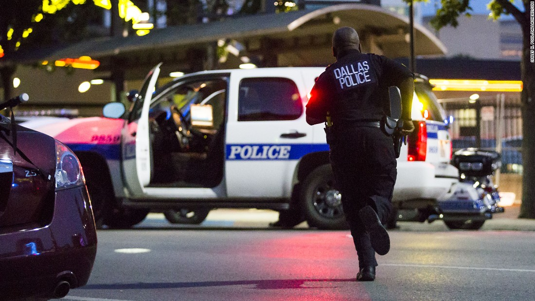 """Dallas Police respond after shots are fired. Pool said, """"At 8:47, I'm shooting the last stragglers from ground level moving down the street, mostly with the police coming back,"""" he said. """"At 8:55, I'm making photographs of police on the ground with their guns drawn because the shots had been fired."""""""