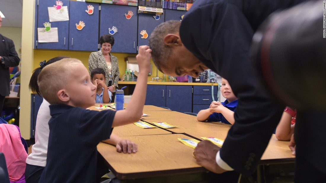 U.S. President Barack Obama leans over for a boy to touch his head during a visit to an elementary school at MacDill Air Force Base in Tampa, Florida, on September 17, 2014.