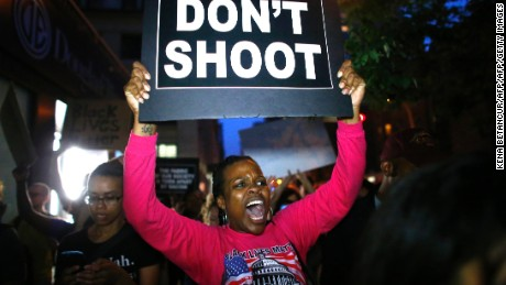 A woman holds a banner during a protest in support of the Black Lives Matter movement in New York on July 09, 2016.