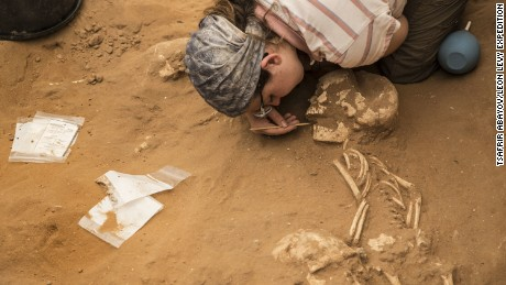 A student archaeologist brushes dirt away from a skeleton buried in the first ever Philistine cemetery, found at Ashkelon in Israel.