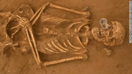 A skeleton, with a small bottle in front of its face, at the Philistine cemetery in Ashkelon, Israel.