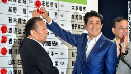 Japanese Prime Minister and ruling Liberal Democratic Party (LDP) president Shinzo Abe (C) places a red paper rosette on an LDP candidate's name to indicate an election victory at the party's headquarters in Tokyo on July 10, 2016. Abe's ruling coalition was on track to expand its majority in upper house elections on July 10, media projections showed, in a convincing victory despite lukewarm support for its policies. / AFP / KAZUHIRO NOGI        (Photo credit should read KAZUHIRO NOGI/AFP/Getty Images)