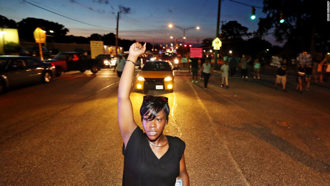 Sirica Bolling raises her fist as she walks down Jefferson Avenue during a Black Lives Matter protest in Newport News, Va., Sunday July 10, 2016, following the fatal shootings of Alton Sterling in Louisiana and Philando Castile in Minnesota.
